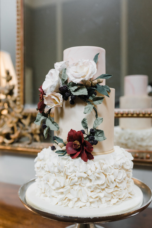 iced wedding cake with red sugar flowers