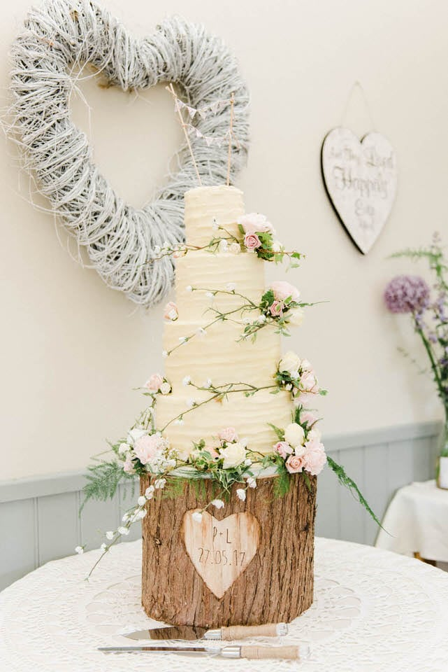 4 tier buttercream wedding cake on log cake stand