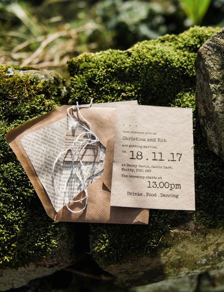 Rustic Yorkshire wedding invites on mossy wall