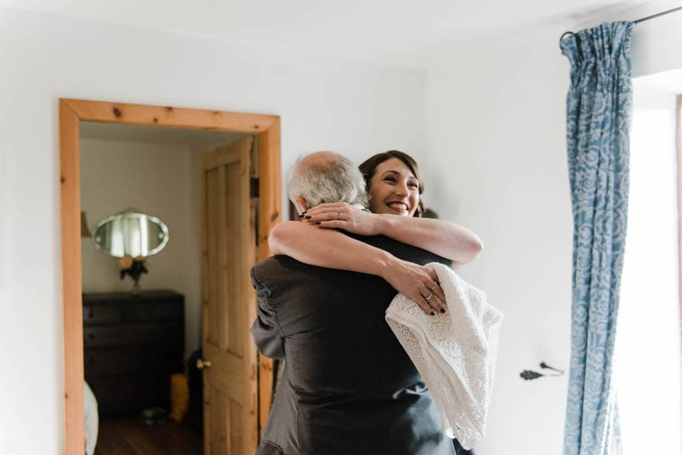 Bride hugging dad in wedding dress