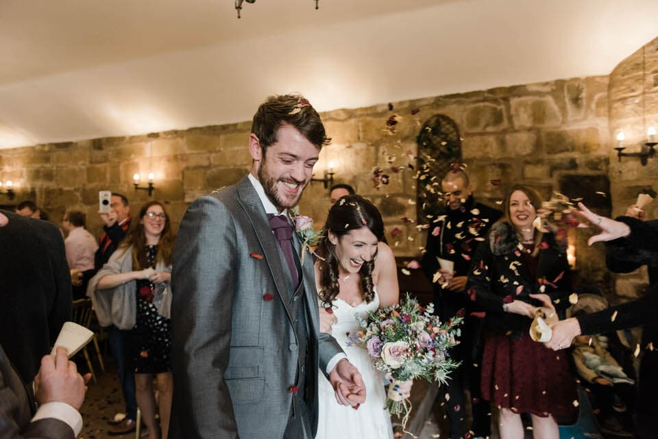 Bride and groom walking out into confetti at Danby Castle