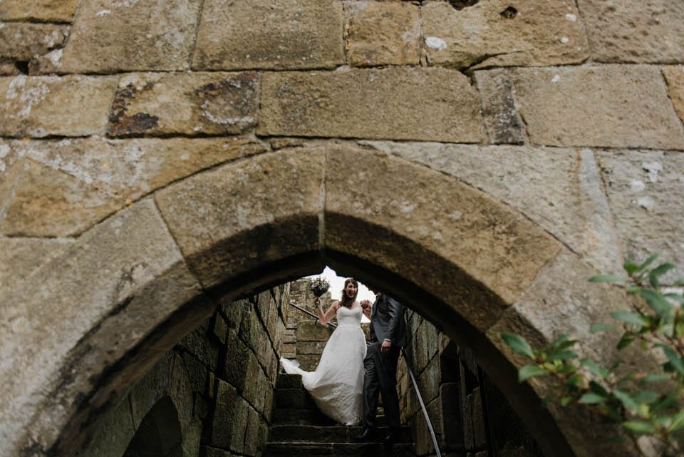 Bride and groom walking down stairs at Danby Castle wedding